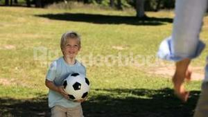 Dad and his son playing with a soccer ball
