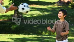 Dad playing with his son with a soccer ball