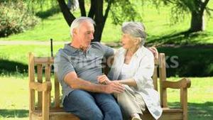Old man and woman talking on a bench