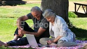 Old man and woman using a laptop sitting on a tablecloth