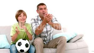In slow motion happy father and son with football watching tv