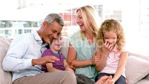 In slow motion happy family sitting on sofa