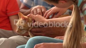 In slow motion happy family sitting with cat on sofa