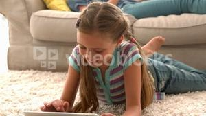 In slow motion happy girl using digital tablet on rug with mother reading book in background
