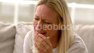 In slow motion woman crying sitting on sofa