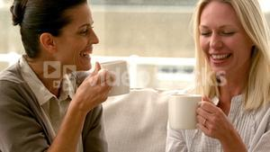 In slow motion two friends sitting on the couch chatting over coffee at home