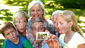 In slow motion man taking picture of his cheerful extended family