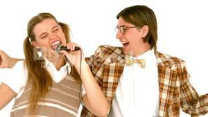 In slow motion happy geeky hipsters singing with microphone