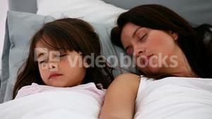 Serene mother and daughter sleeping together