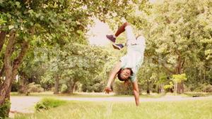 In slow motion cool young break dancer doing back flip in the park