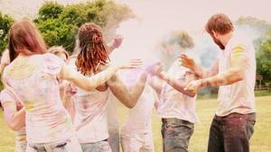 In slow motion happy friends throwing powder paint