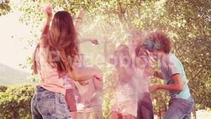 In slow motion happy friends covered in powder paint