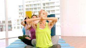 Yoga class raising their hands
