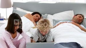 Attentive children using a laptop while their parents are sleeping