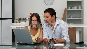 Happy couple looking at their accounts online wile sitting at the table