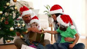 Cute family opening Christmas presents sitting on the floor