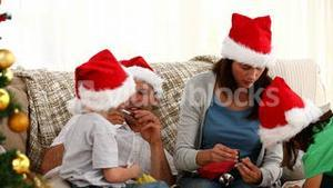 Family opening Christmas presents sitting on the floor