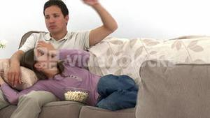 Nice couple watching television with popcorn