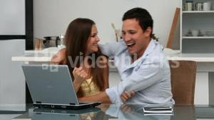 Lovely happy couple looking at the laptop sitting at a table