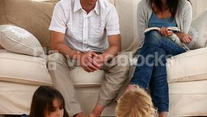 Parents talking each other sitting on the sofa