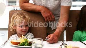 Father trying to convince kids to eat vegetables