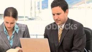 Business people working together with a laptop and a notepad