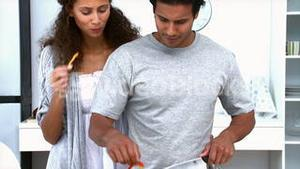 Woman eating while her husband is cooking vegetables
