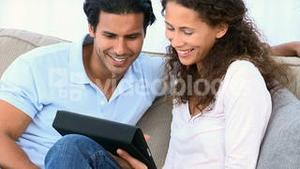 Couple using a computer tablet sitting on the sofa