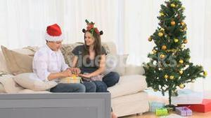 Woman opening a gift that her husband gave to her