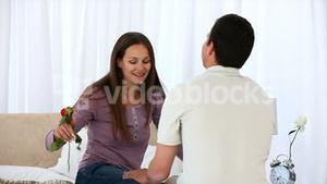 Man giving a rose to his wife sitting on the bed