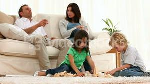 Parents talking together while their children playing