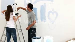Couple painting a wall in blue