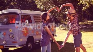 In high quality format hipster couple making heart with arms