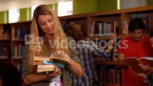 Smiling student reading books