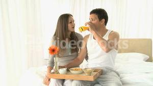 Man drinking orange juice while he having breakfast with his wife