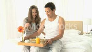Woman drinking orange juice while she having breakfast with her husband