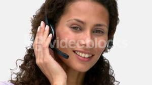 Closeup of a smiling businesswoman talking with headphones