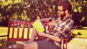 In high quality 4k format handsome hipster reading in the park