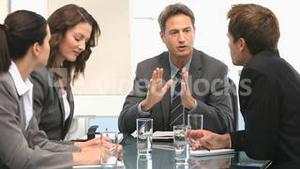 Businesswoman and businessman talking around a table