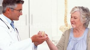Doctor showing patient how to exercise injured hand