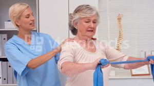 Physiotherapist examining elderly patients back