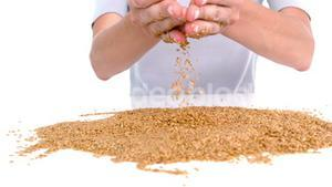 Woman pouring grain on white background