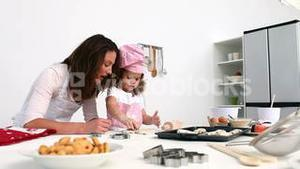 Daughter and mother baking cookies