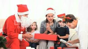Family opening gift with Santa Claus