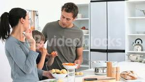 Family eating vegetables while they prepare lunch
