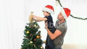 Father helping his son to decorate the Christmas tree