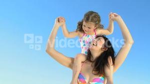 Mother carrying her daughter on her shoulders