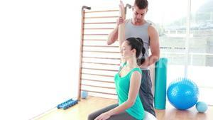 Trainer assisting woman exercising on fitness ball