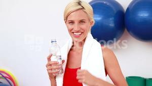 Blonde woman drinking water with thumbs up