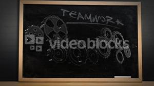 Cogs and wheels turning on blackboard